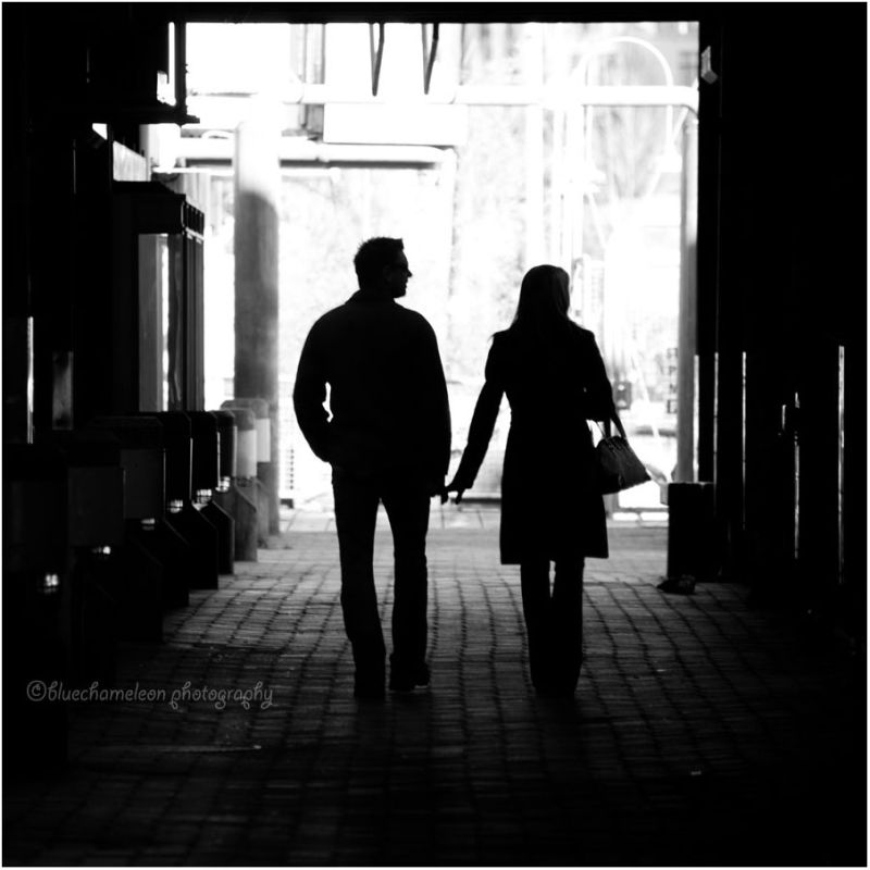 Silhouetted couple touching hands thru corridor