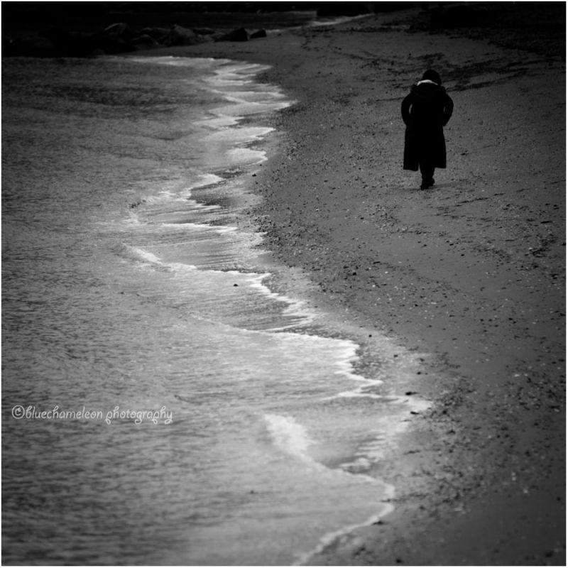 A woman in black walking along the shore line