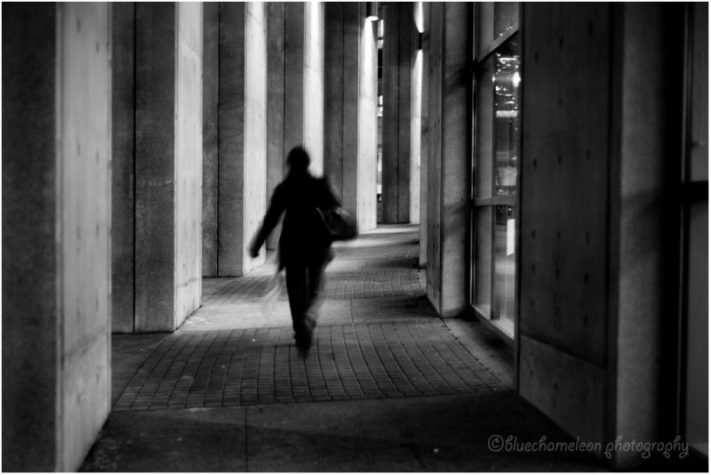 A silhouetted woman walking quickly through column