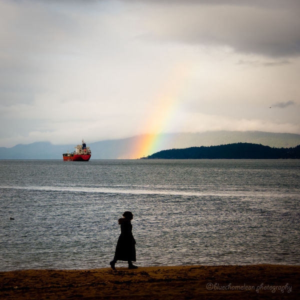 A woman walking along the beach with a rainbow