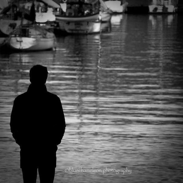 Silhouetted man against a harbour full of boats
