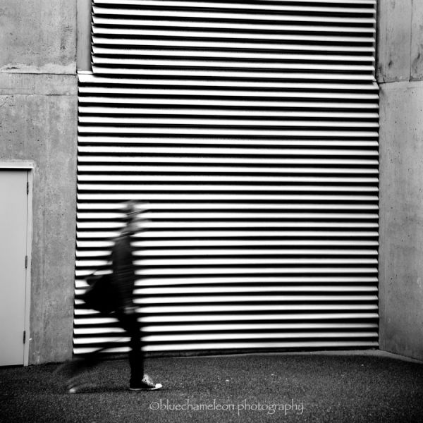 A blurred man walking by steel door