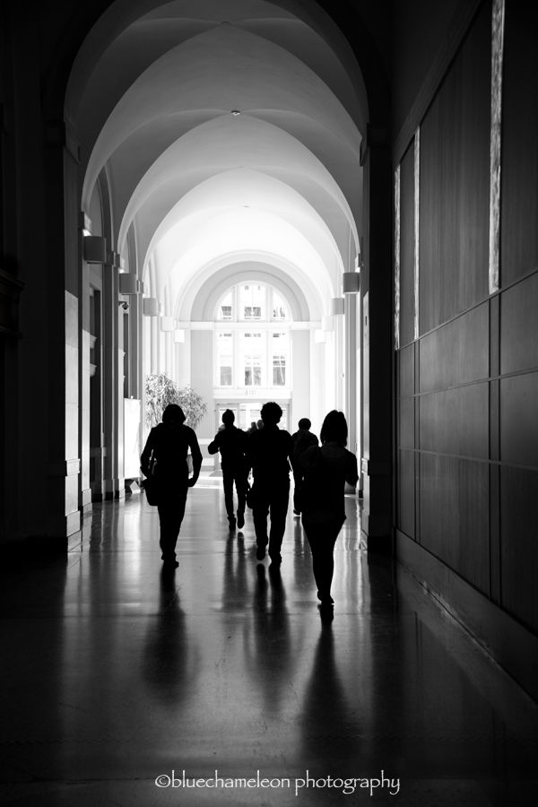 silhouetted people walking through archways