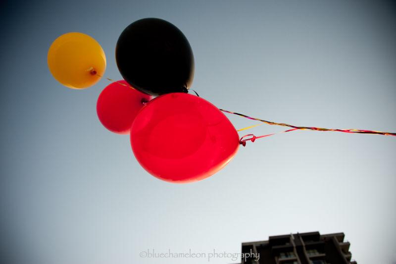 Colourful balloons escaping into the blue sky