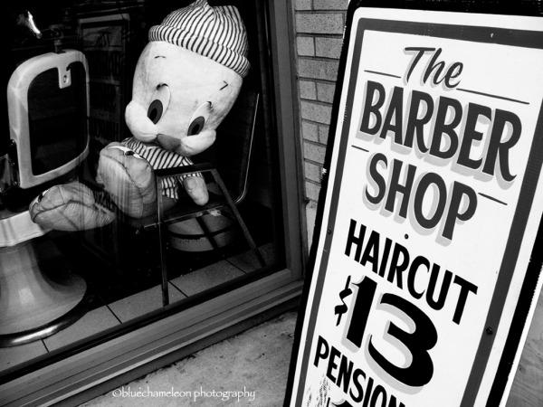 A giant tweetie bird sitting in barber shop window