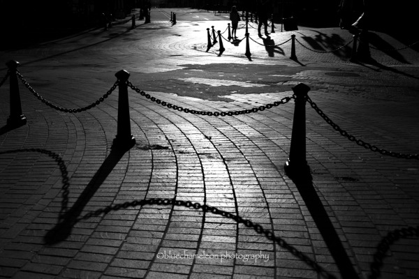 Chain fences and their shadows on city streets