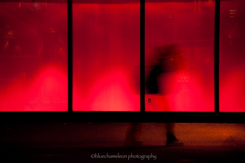 A blurred moving figure against red light windows