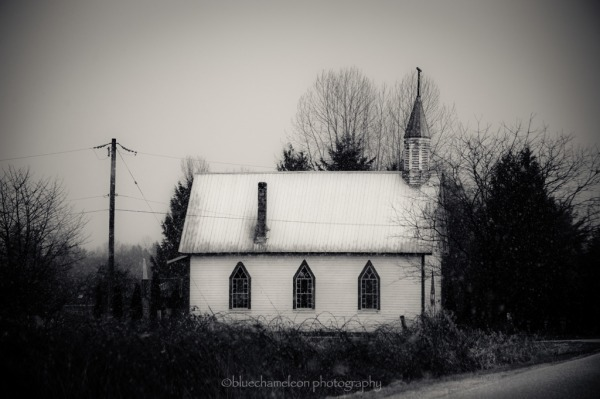 A little wooden church in snow on country road