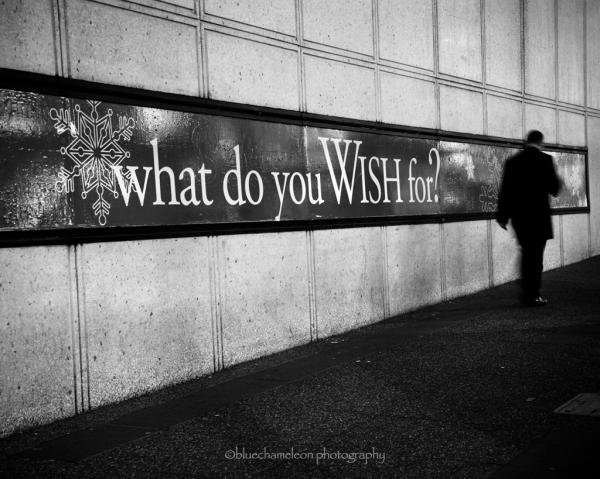 A blurred man walking past wish sign