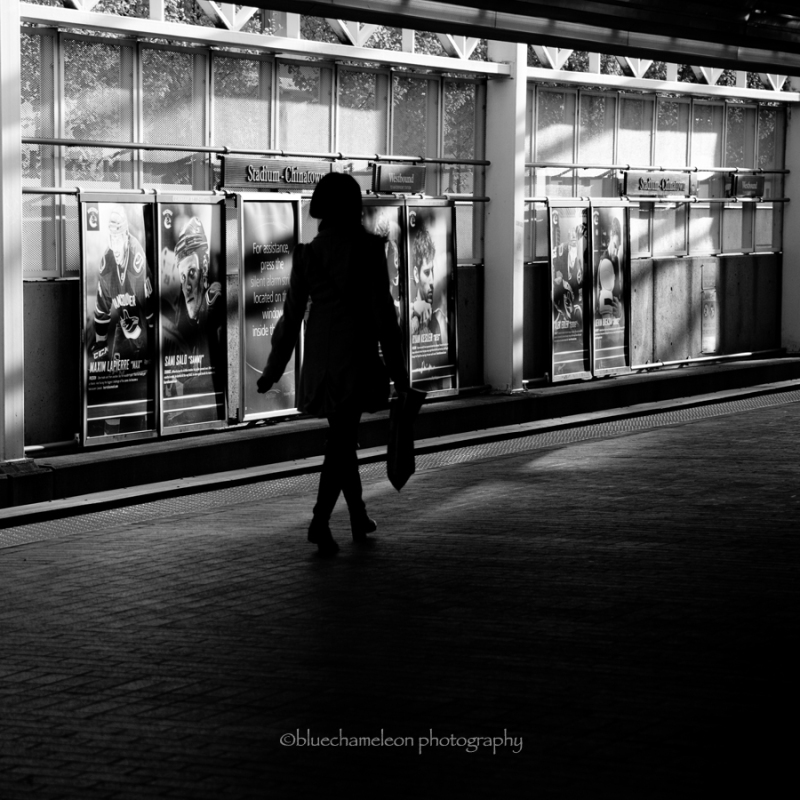Silhouetted woman walking through train station