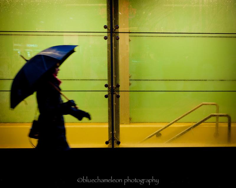 Silhouetted woman walking past window in rain