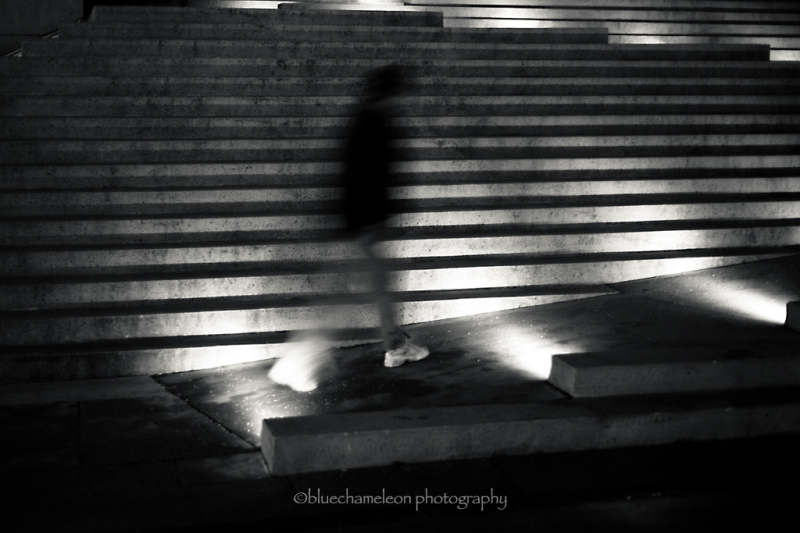 Blurred man walking against lit stairs