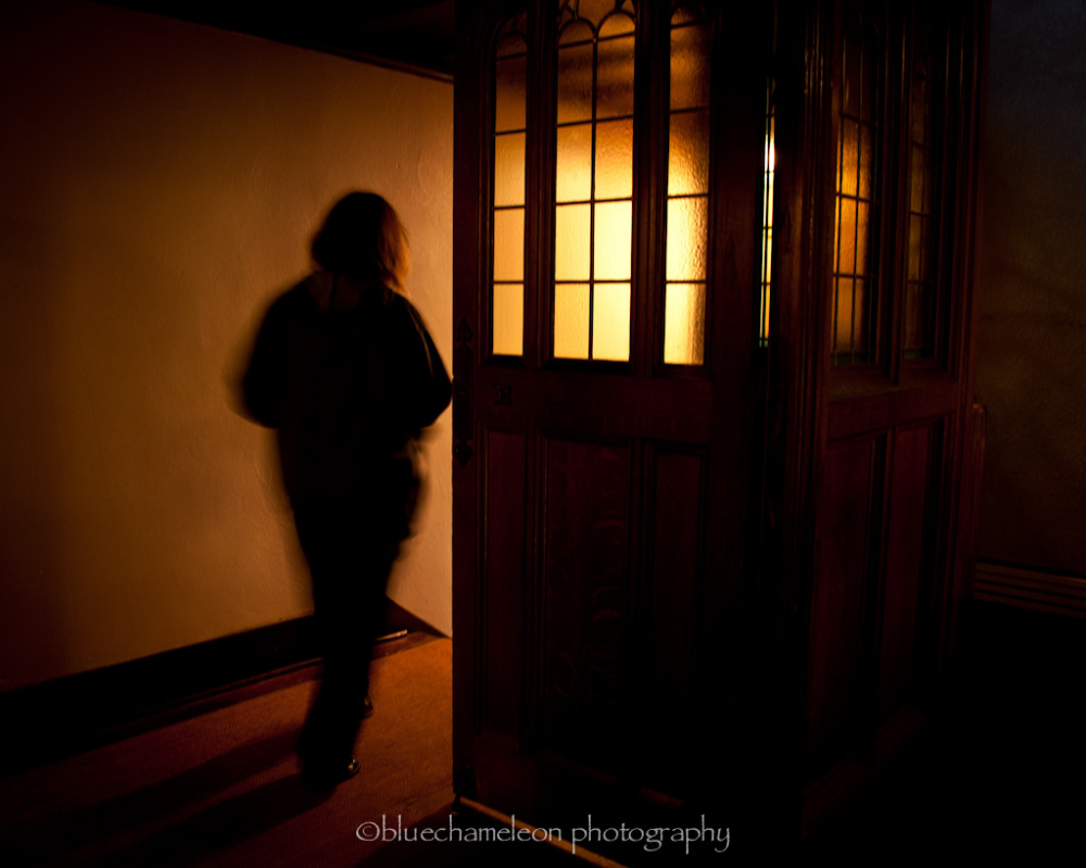 A blurred woman walking through light in church