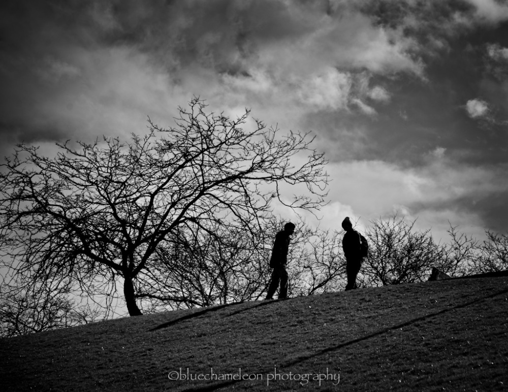 2 silhouetted metting on the side of a hill