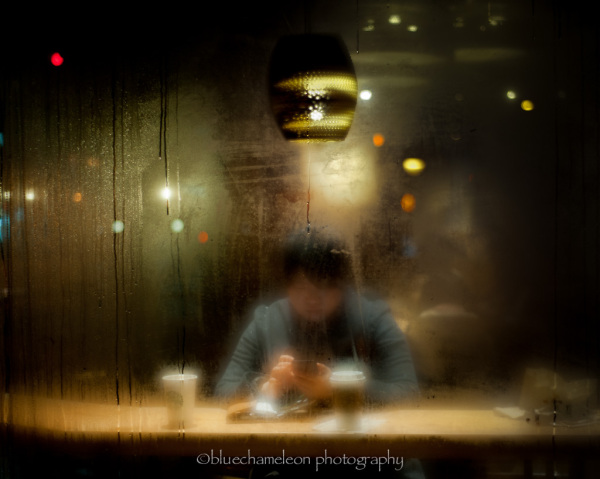 A man sitting in coffee shop with fogged window