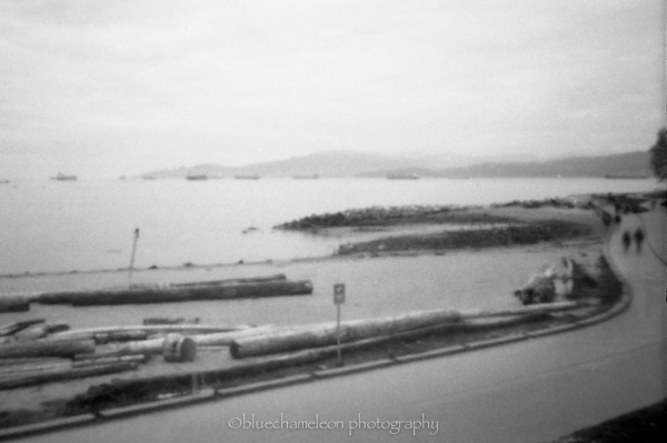 Pinhole image of a seawall and people walking