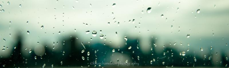 Rain drops on window and blurred skyline