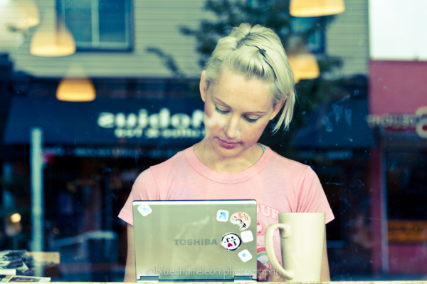 Woman sitting at cafe with laptop through window