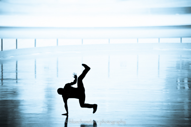 A silhouetted man in break dance pose in street