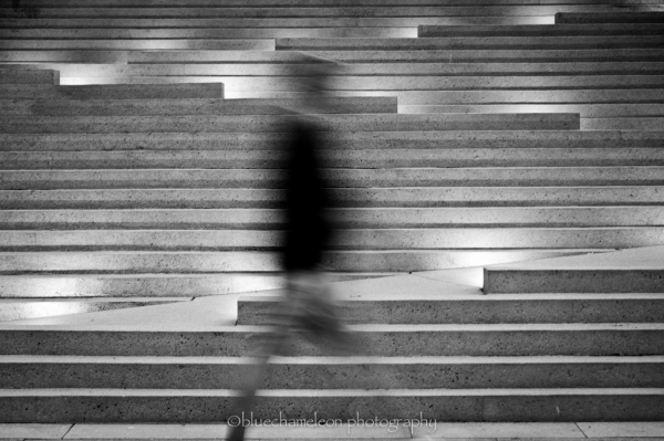 A blurred man walking across stairs lit up