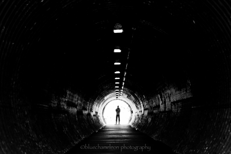 A lone silhouetted man at end of long tunnel