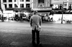 Man standing in middle of busy city street