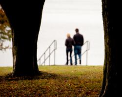 A couple walking toward ocean through fall leaves