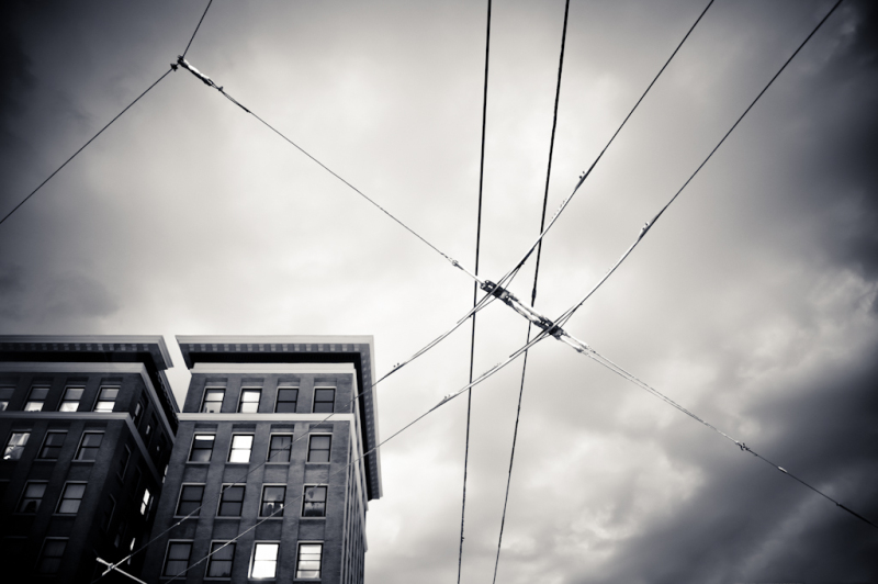 Trolley wires in sky with buildings