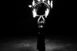 A woman holding ring of fire above her head