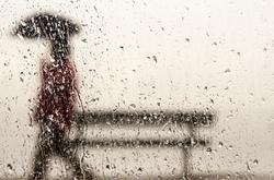 A blurred man through raindrops with umbrella