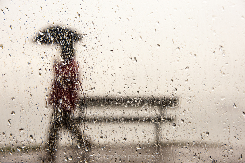 A blurred man through raindrops with umbrella