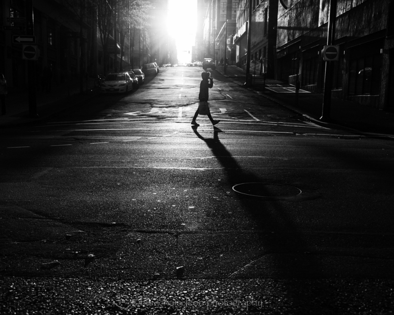 Silhouetted person and long shadow crossing street