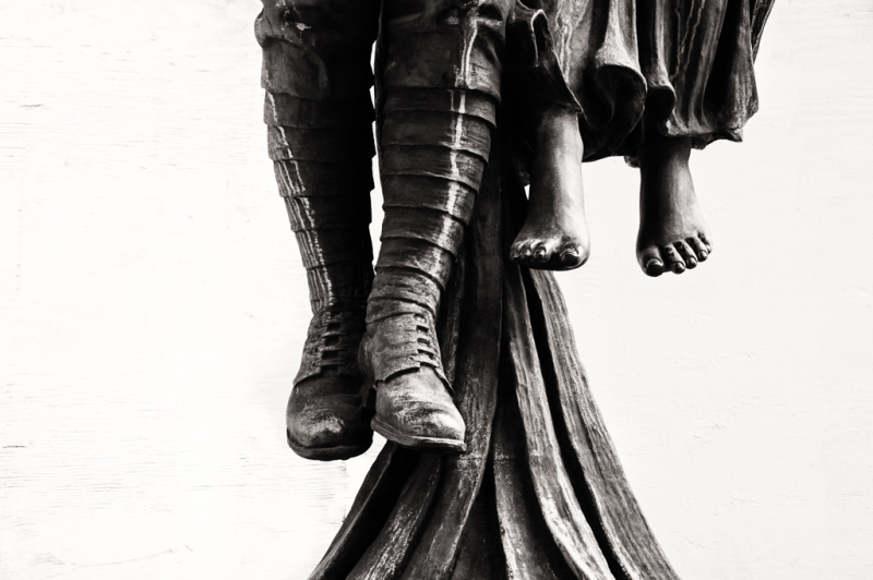 Dangling legs and feet of a sculpture in the city
