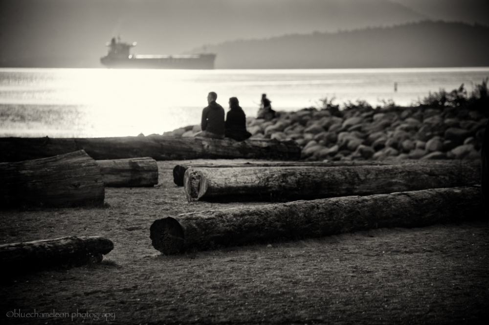 2 silhouetted people on beach watching ship