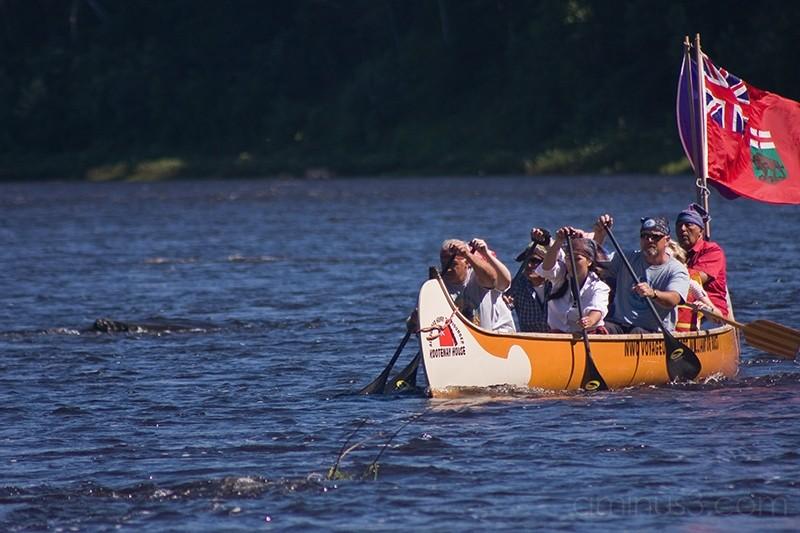 Voyageurs paddling in canoe