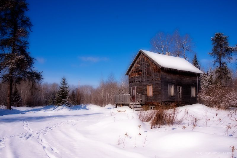 Old wooden house in winter landscape