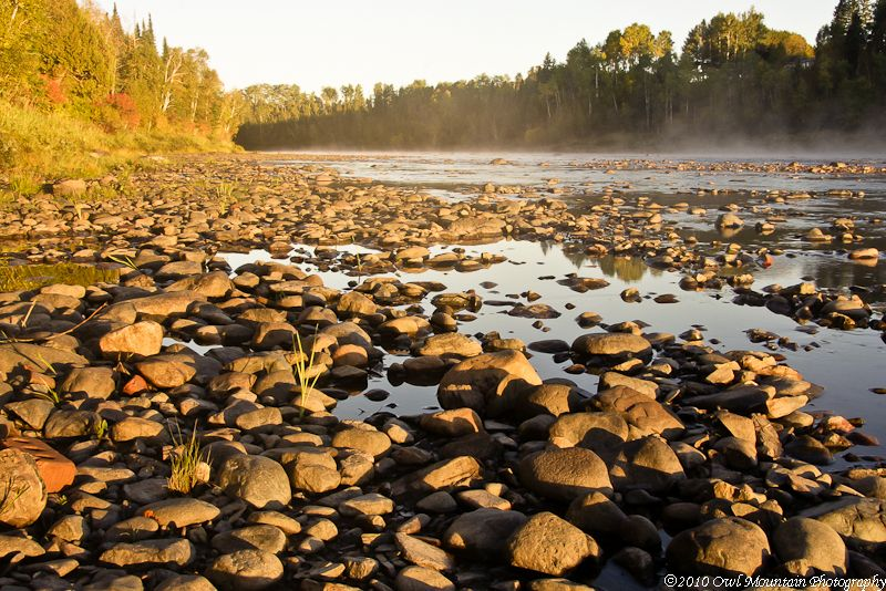 early morning mist on river with rocks in foregrou
