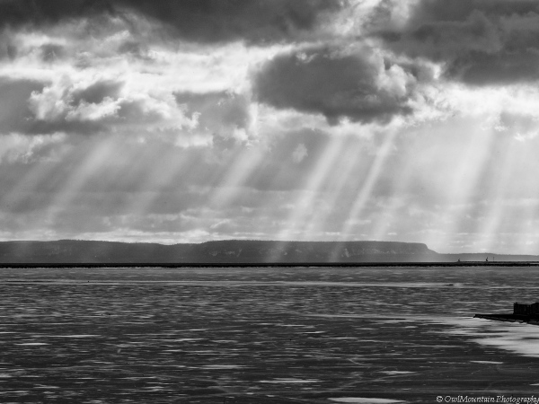 sun rays through clouds over frozen lake