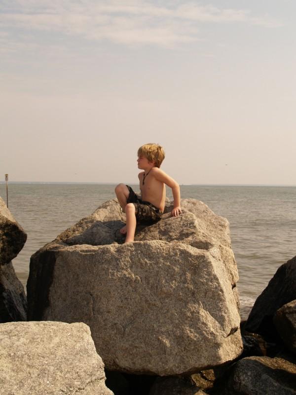 Blond boy on a big rock at the beach.