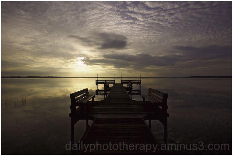 Pier on lake at sunrise