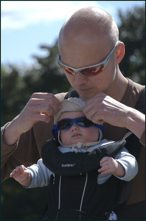a father holding his chiled wairing sun glasess