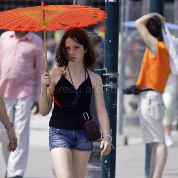 a young walking tourist holding an orang umbrella