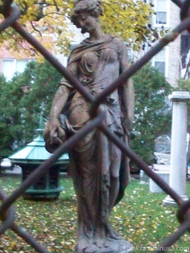 Statue and chain link fence