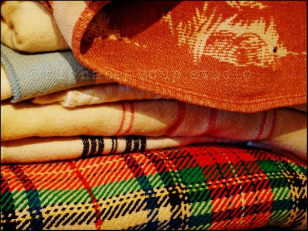 stack of folded patterned blankets in junk store
