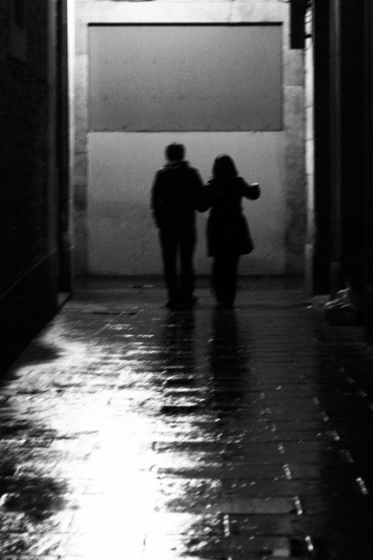 people couple night light walk city street