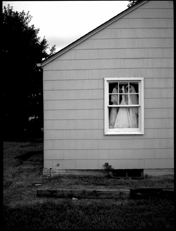 fancy dresses in a house window - b&w photo