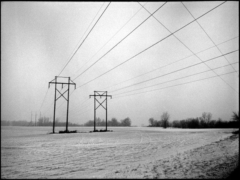 power lines in a snowy field - b&w photo