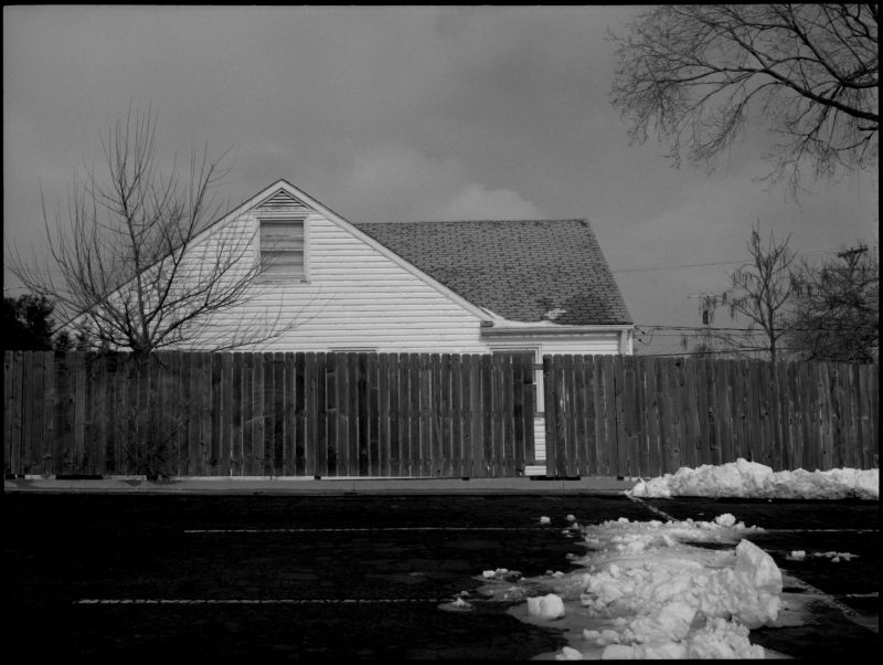 house and parking lot in snow - b&w photo