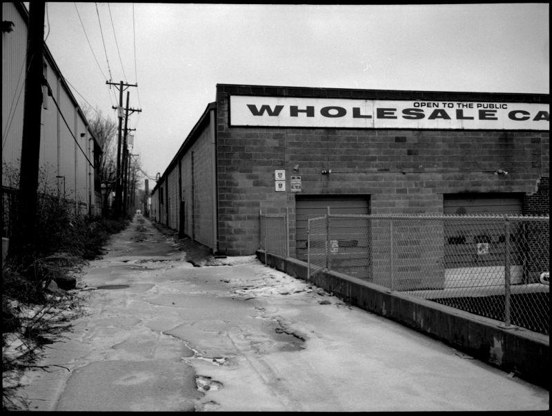 snowy alley industrial building photo b&w