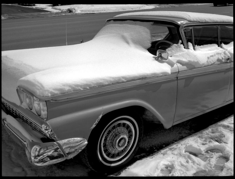 antique car in snow, black & white photo, old car